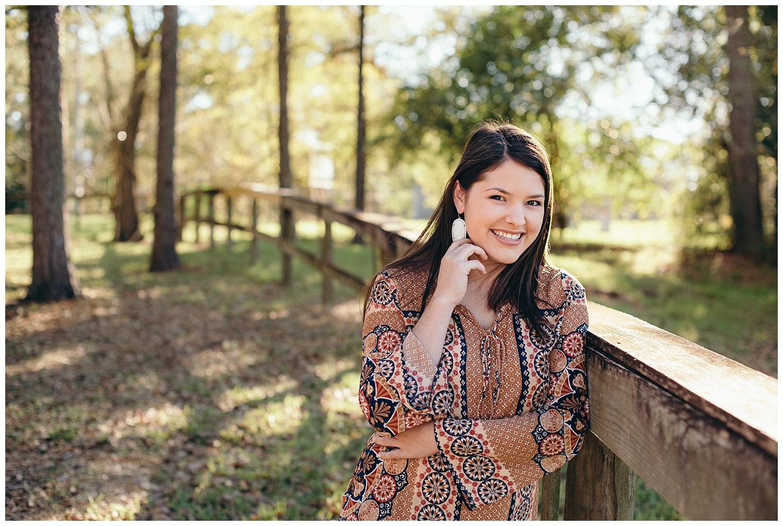 lively park portrait of a senior girl against a wooden fence