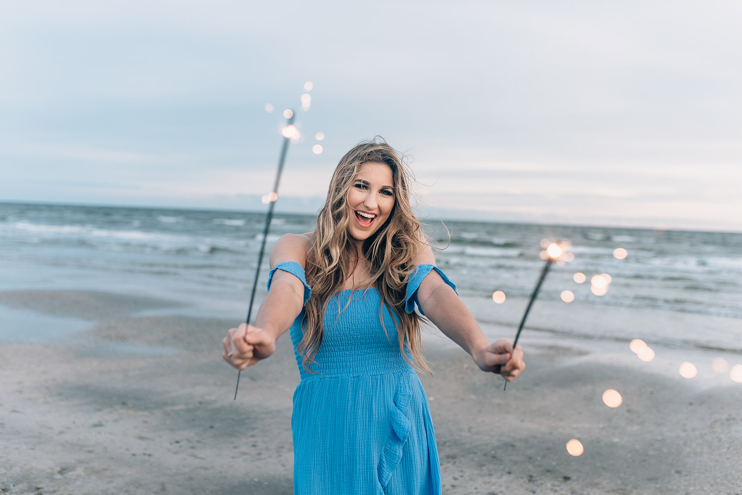 senior girl with sparklers at her senior session in Galveston