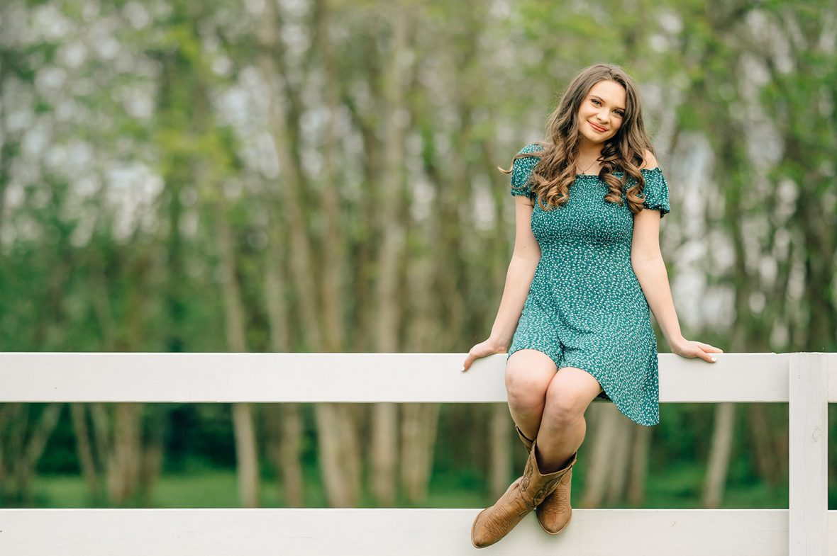 girl smiling on white fence in green dress and cowgirl boots