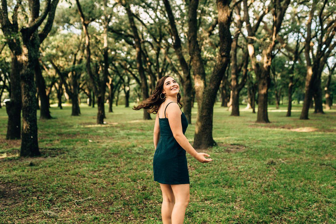 senior girl twirling in the woods of Houston