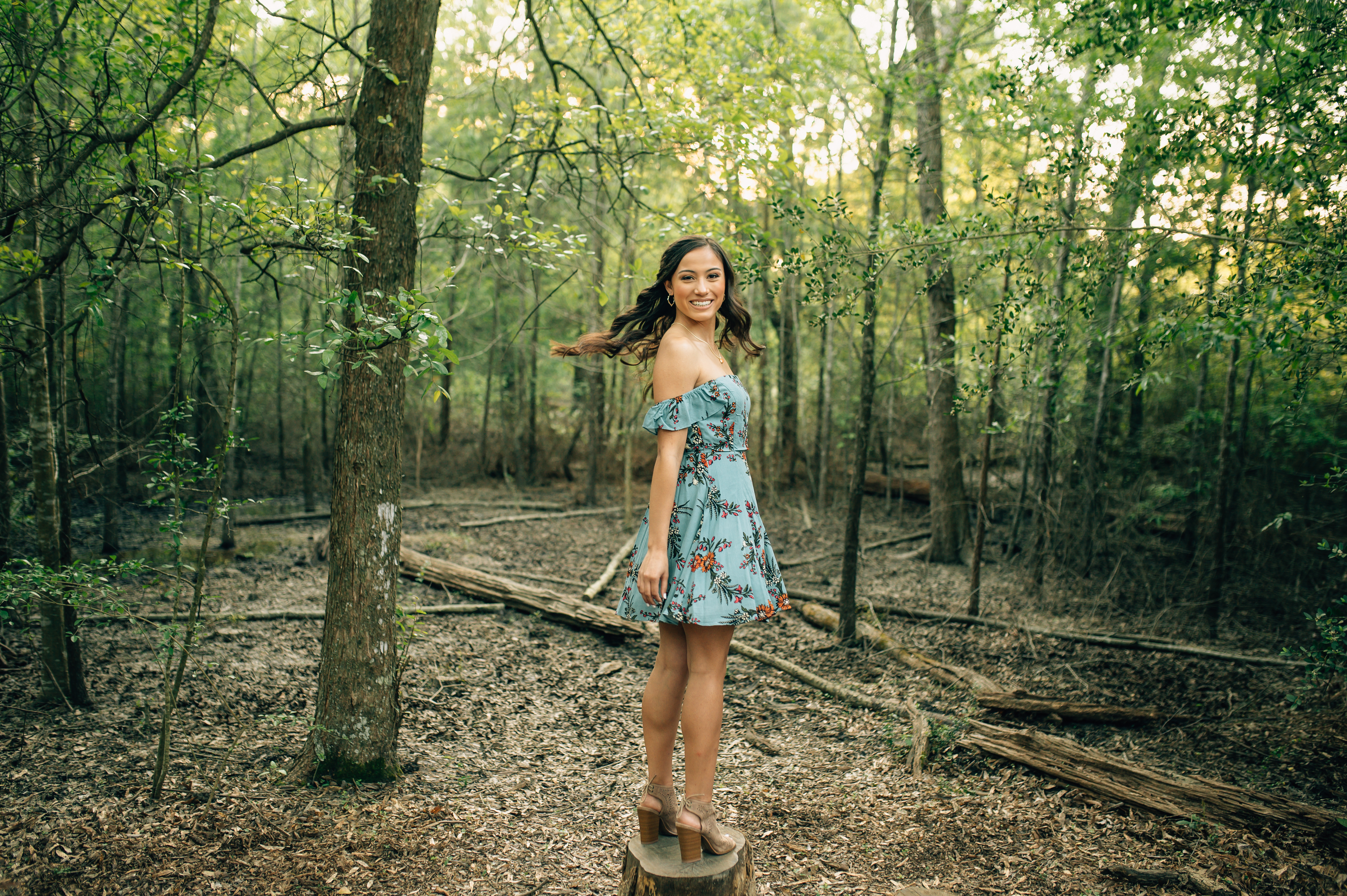girl in the woods spinning around