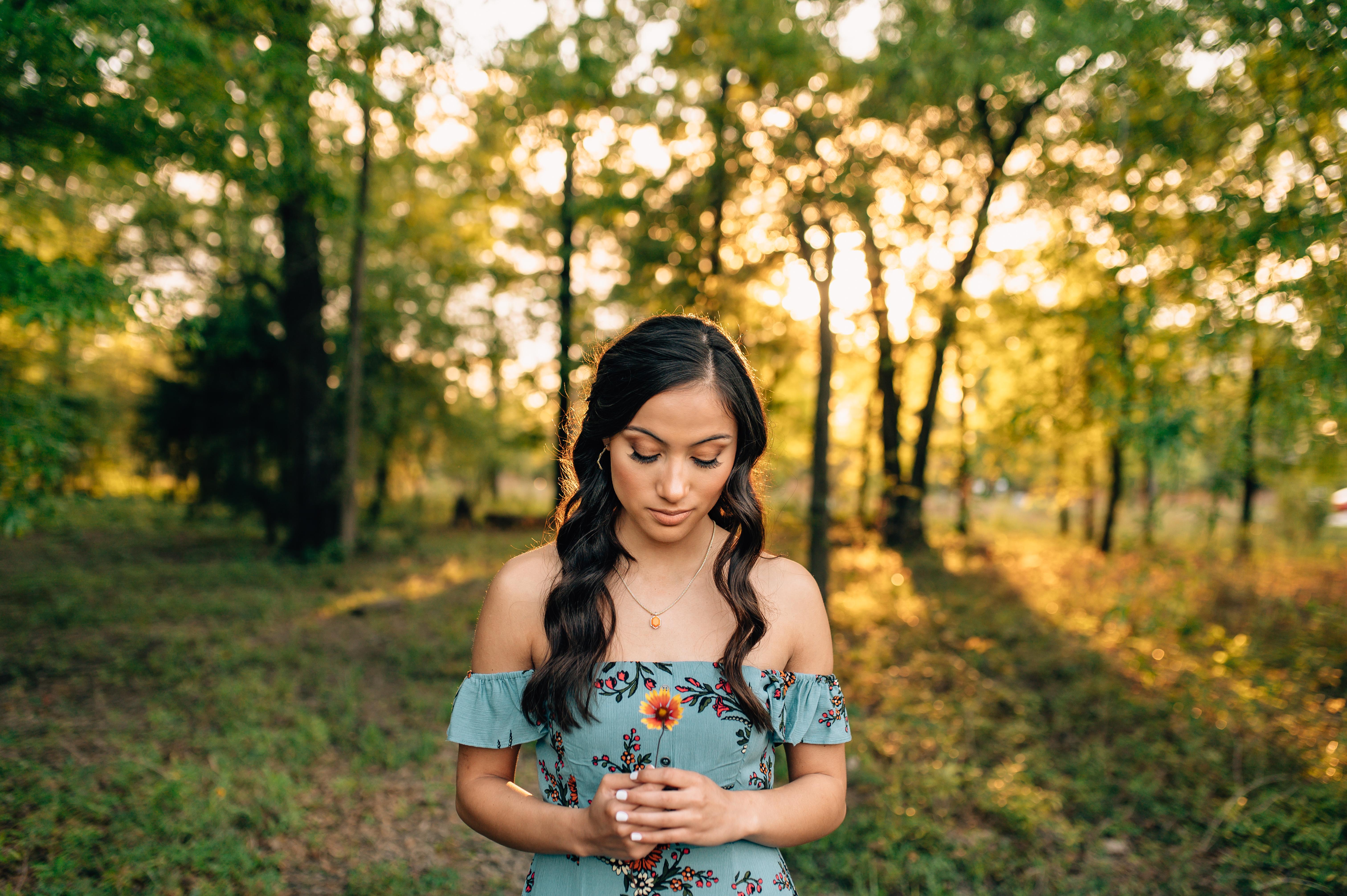 senior girl from Houston holding flowers in the woods