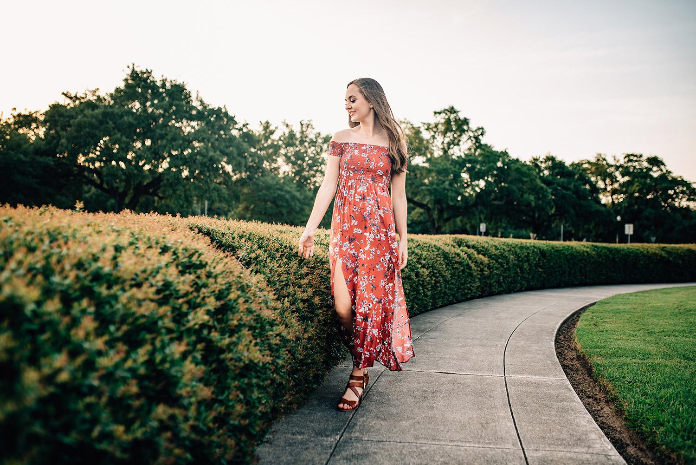 senior girl wearing red dress walking in her senior portraits in the summer