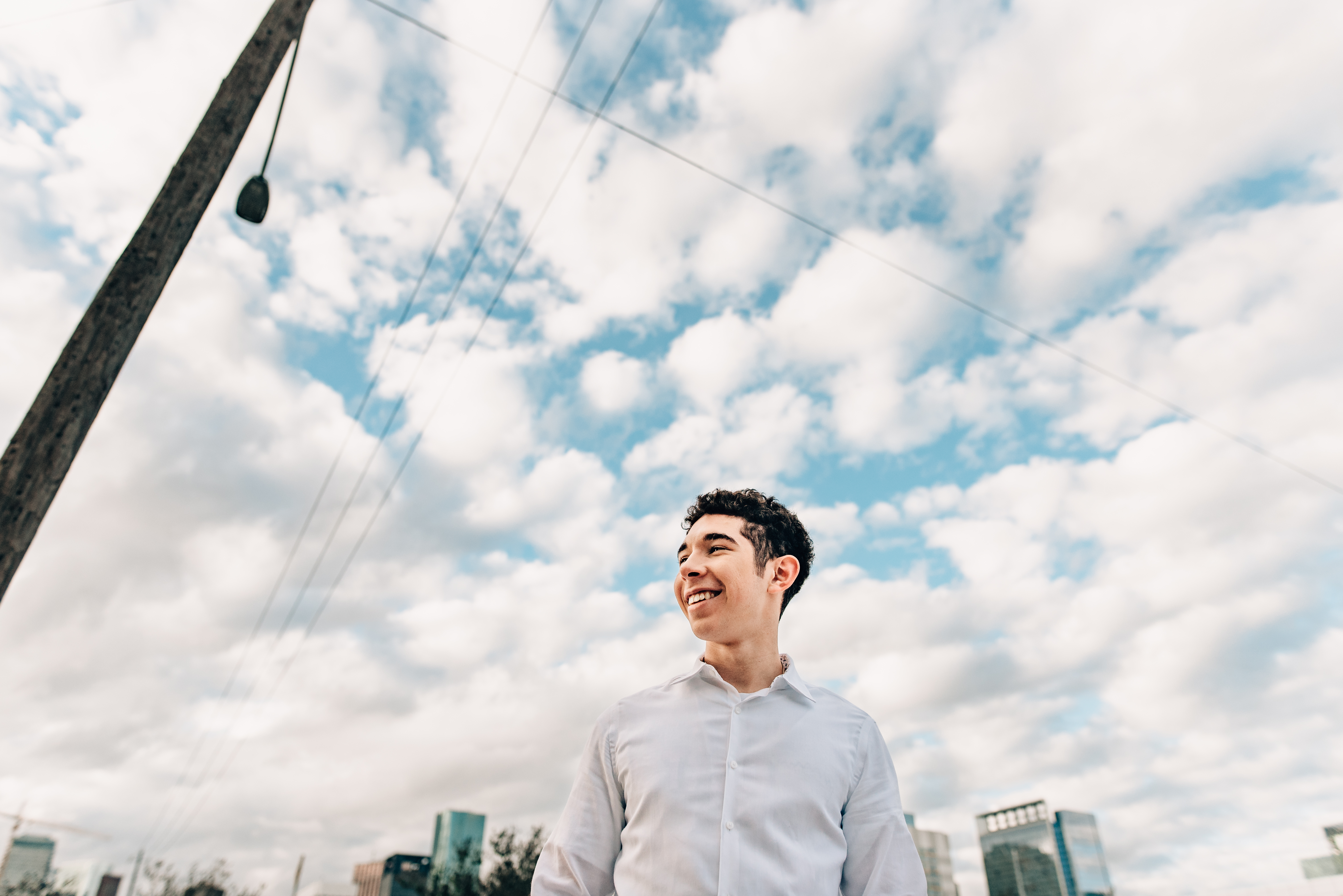 senior guy with white button down shirt smiling with the sky behind him