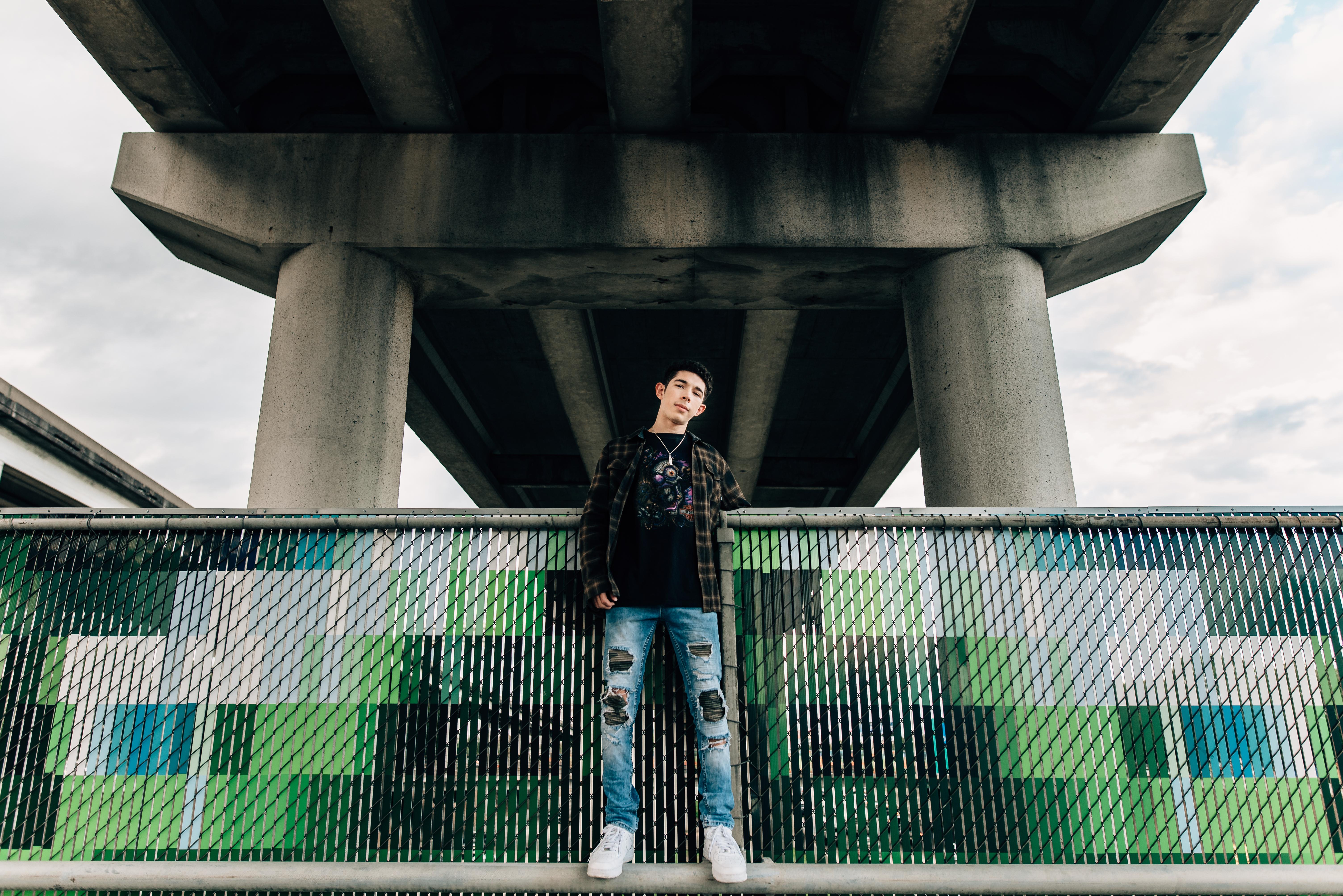 teenage boy standing underneath a bridge overpass