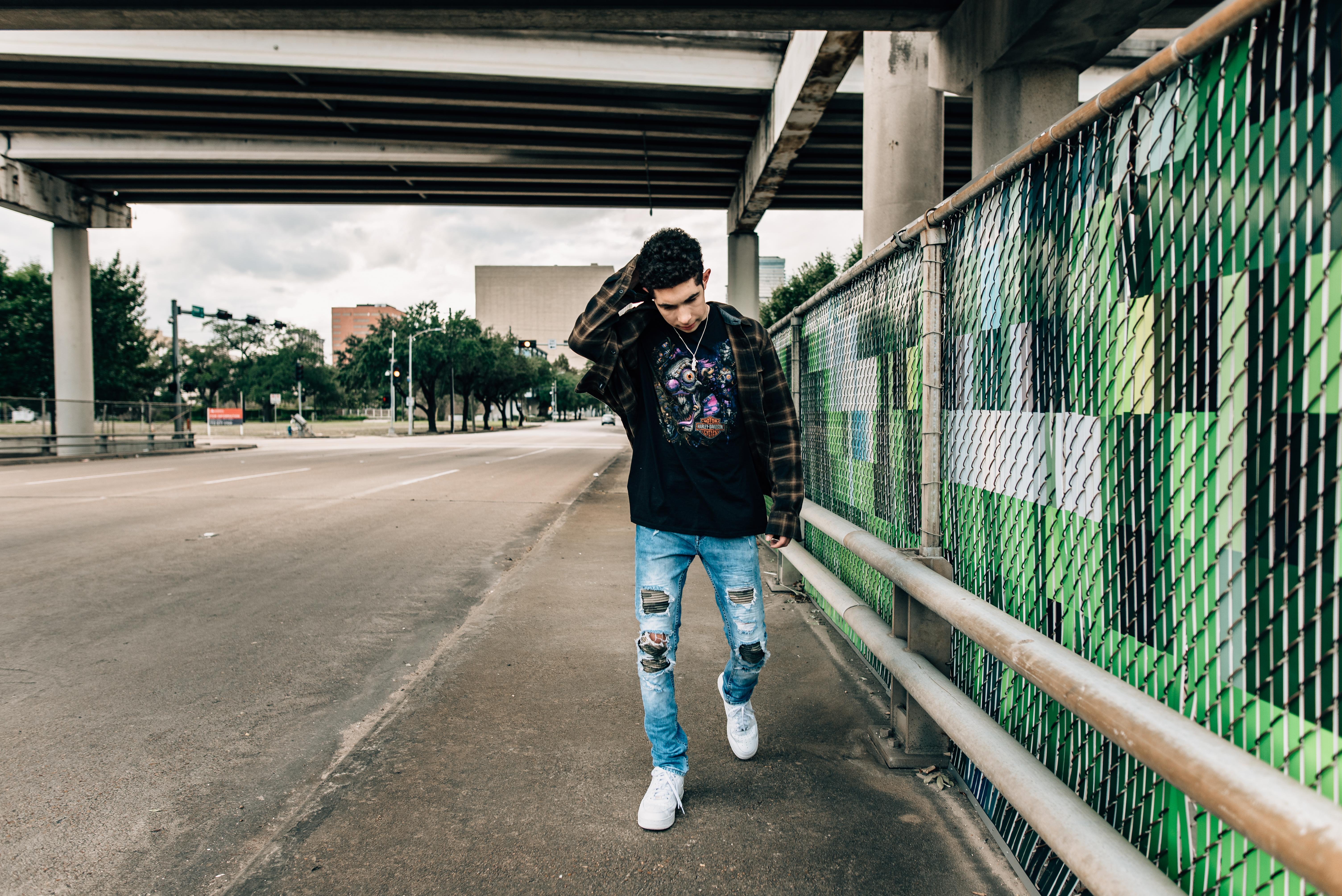 teenage boy walking under an overpass
