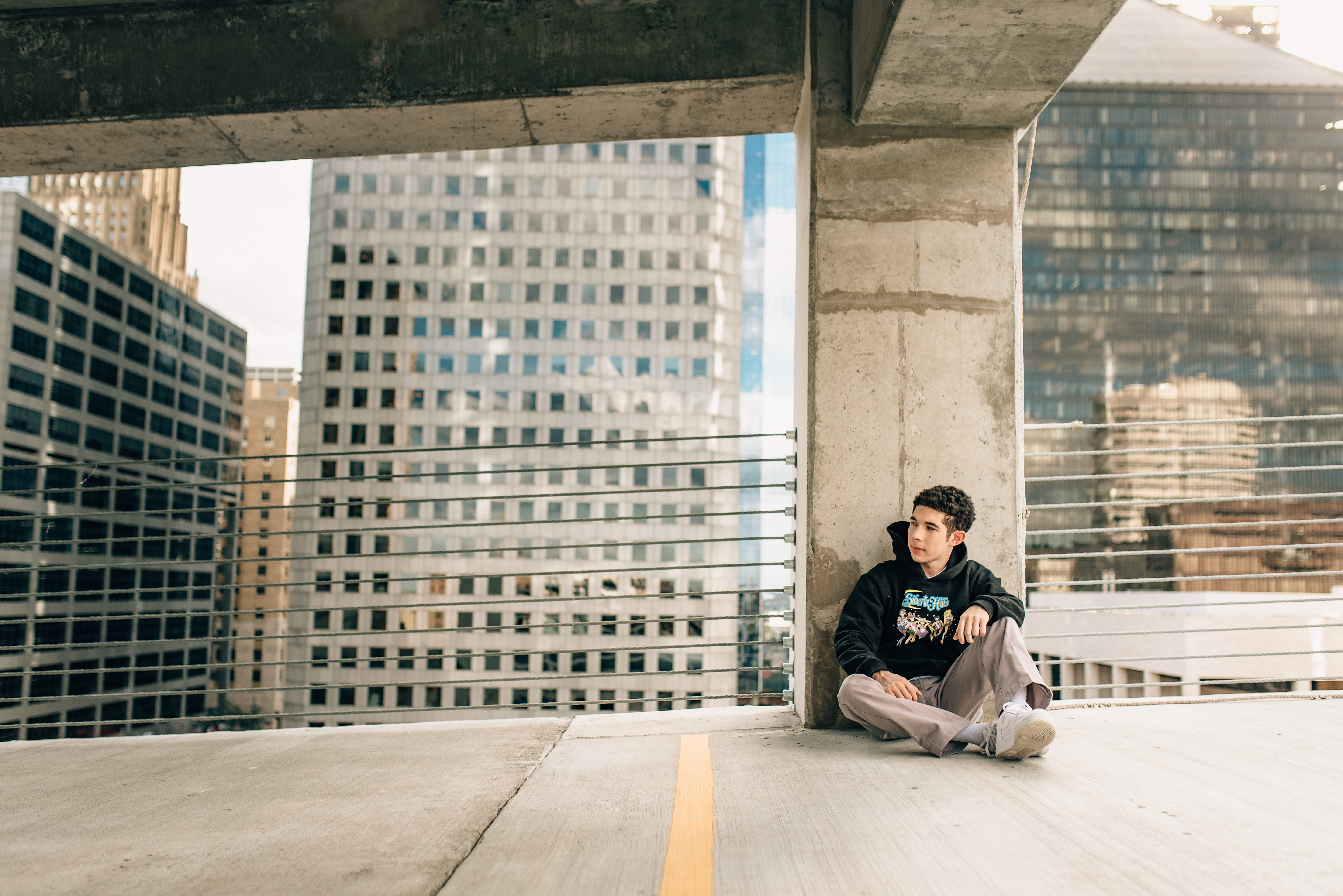 guy sitting in a parking lot with the city behind him