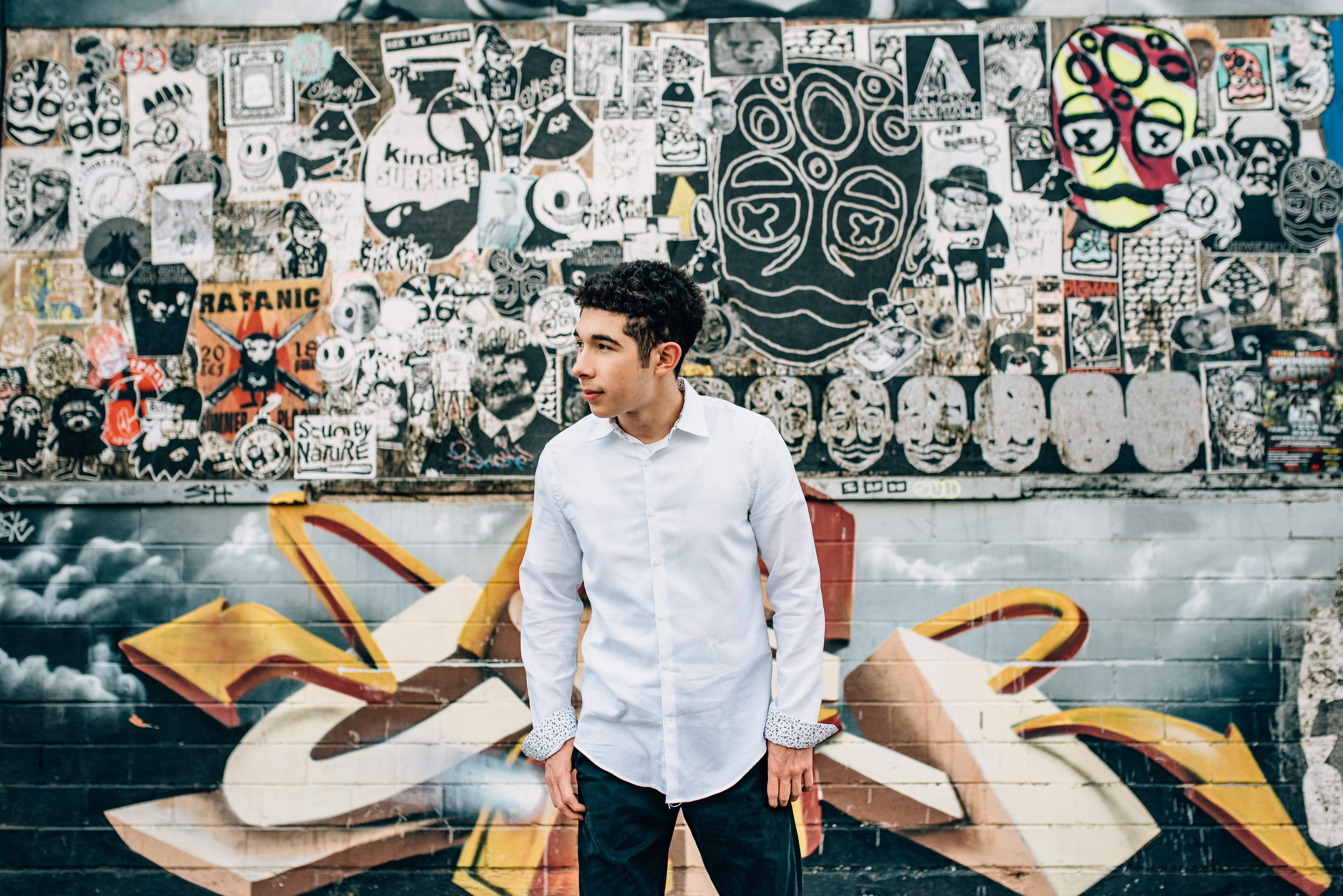 guy in white button down shirt standing in front of graffiti wall